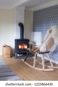 Blurred background photo of Scandinavian interior: wood burning stove, box of firewood, white sheep skin in old rocking chair in living room. Striped rag carpet on oiled wooden floor.