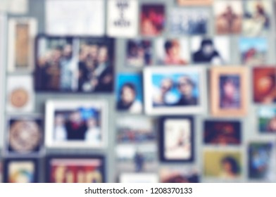 Blurred background with postcards and photos in frames put up on a wall. Collage of pictures with loved ones, friends or family. Concept for keeping good memories about holidays or vacation.