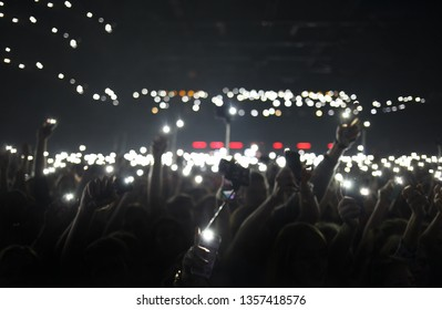 Blurred background poster with concert crowd waving hands with mobile phone lights.Blurry wallpaper with smartphones  on dancefloor.Big group of young people partying on edm festival in nightclub