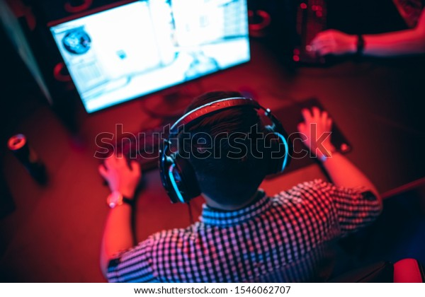 Blurred background professional gamer playing tournaments online games computer with headphones, red and blue.