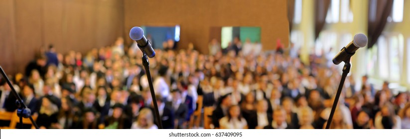 Blurred background of public event exhibition hall show concept with microphones. Panorama view.