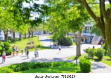 Blurred background of a public park with people walking in a beautiful summer day
