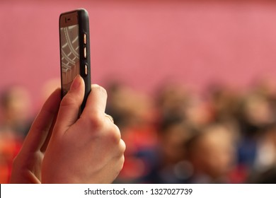 Blurred background. Reportage photo or video shooting on a mobile phone. The hands of the girl hold the smartphone in selfie mode or broadcast live in the auditorium or the gym with people. Copy space