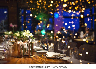 Blurred background of restaurant, bar or night club with colorful lights bokeh. Abstract defocused blur background. Selective focus. Christmas dinner, festive table setting with flowers decorations.