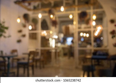 Blurred background : Restaurant with tables and chairs blur background with bokeh light. Evening time