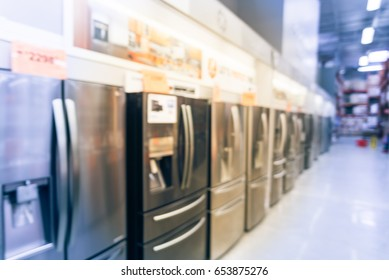 Blurred background retail store with rows of home appliances equipments. Defocused brand new wide selection of French door refrigerators with ice makers. Row of fridges with price tags on display.