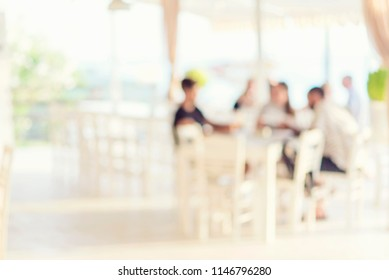 blurred background of scene in a restaurant, blurred unrecognizable people sitting at the table in the garden