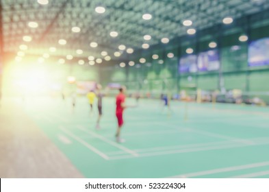 Blurred background of the shuttlecock and badminton courts with players competing in modern gym