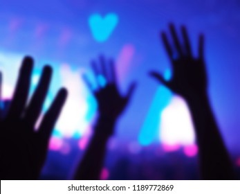 Blurred background of silhouette hands of audience at live concert or nightclub with bokeh defocused lights. Enjoy Music and Entertainment Concept. (Space for text or abstract background for design)