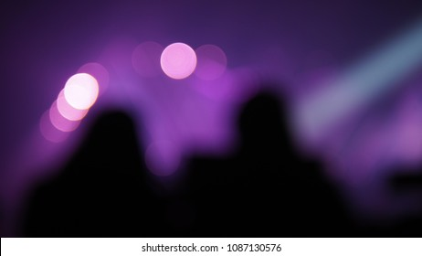 Blurred background of silhouette people or audience at live concert in music hall with bokeh defocused lights. Enjoy Music and Entertainment Concept. (Space for text or abstract background for design)