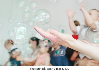 blurred background of Soap bubbles blown by a child. woman hand Bubble show for birthday party. Professional presentation with blowing large soap bubbles. kids catch, have fun joy