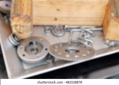 Blurred background Steel gears, nuts, bolts, and wrenches. pieces of equipment in the system.