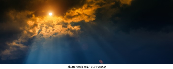 blurred background, sun and rays on a dark background of thunderclouds. Horizontal banner.