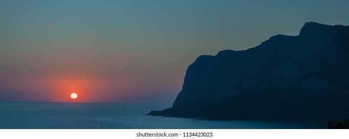 blurred background, sunset and silhouettes of mountains, seascape. Horizontal banner.