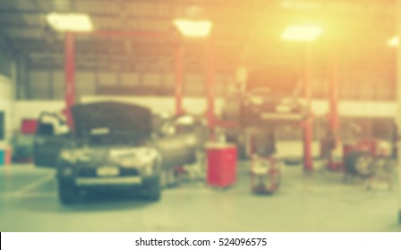 Blurred background of technician repairing the car in garage,mechanics fixing machine in a workshop,auto suspension detail of lifted automobile at service station,vintage color.
