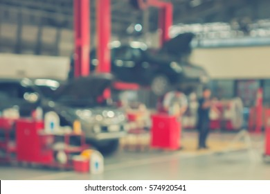 Blurred background of technician repairing the car in garage,mechanics fixing in a workshop suspension detail of lifted automobile at service station,vintage color.