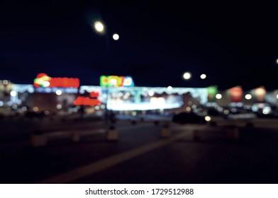 Blurred background. Territory of the shopping center. Night illumination.