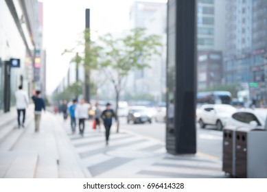 Blurred background of traffic on the road and people walking on sidewalk in city, perspective.
