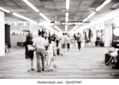 Blurred background : Traveler with baggage at airport terminal blur background with bokeh light.