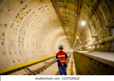 Blurred background of underground tunnel construction.Transport pipeline by Tunnel Boring Machine for electric train subway with control engineer or security safety .