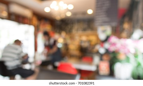 Blurred background of waitress serving food to the customer in the cafe
