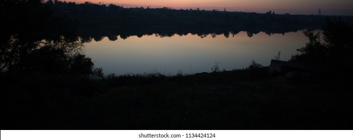 blurred background, water surface in a river and dark shores at dusk, rural landscape. Horizontal banner.