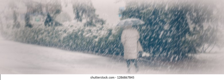 Blurred background, a woman walks with an umbrella down the street in snowy weather. Winter season. Cityscape. Banner for design.