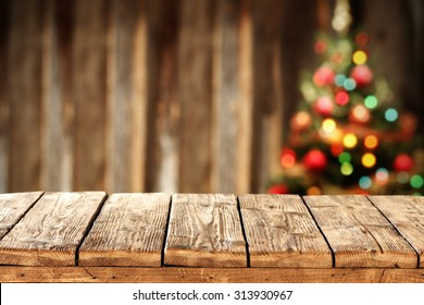 blurred background of xmas tree lights and wall with free space on wooden worn table
