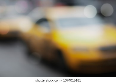Blurred background with yellow taxi cars silhouette in the city street.Out of focus urban transport