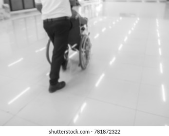 blurred background young man pushing a wheelchair and seniors woman sitting in wheelchair.