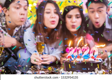 Blurred background of young people blowing candles with numbers 2020 on the birthday cake