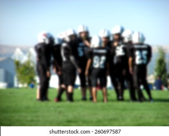 blurred background with youth american football players in action