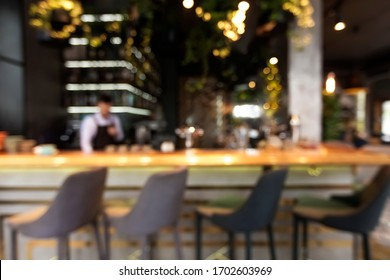 Blurred bar counter with alcohol bottles assortment. Barroom in restaurant, hotel, pub copy space. Cafe background