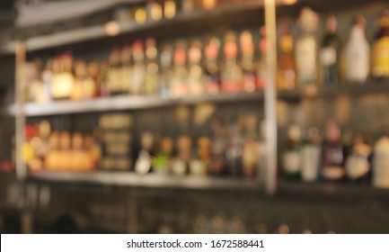 Blurred bar shelves and bar counter with many bottles of liqueurs