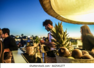 Blurred barman working in chiringuito bar at sunset beach party - Concept of nightlife with cocktails and music entertainment in summer vacation - Warm filter - Defocused image
