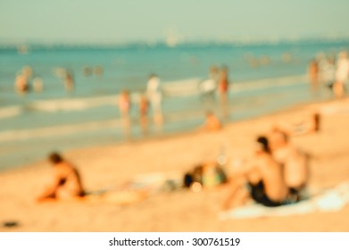 Blurred beach photo with bokeh. People relaxing on beach. Vacation background (Trouville-sur-Mer, Normandy, France) Retro aged photo.