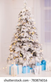 Blurred beautiful glowing Christmas tree and many gift boxes under it in holiday home interior. Vertical color photography.