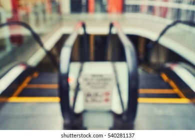 Blurred beautiful lobby at the malls. Escalators. Blurred showcases fashion boutique with clothes. Blurred bokeh basic background for design
