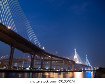 Blurred Bhumibol bridge with floodgate illuminate with spotlight at night scene, Samut Prakarn,Thailand