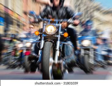 blurred bike riders rushing at city street