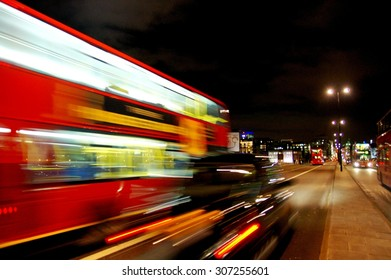 Blurred black taxi and red bus racing in the London city center