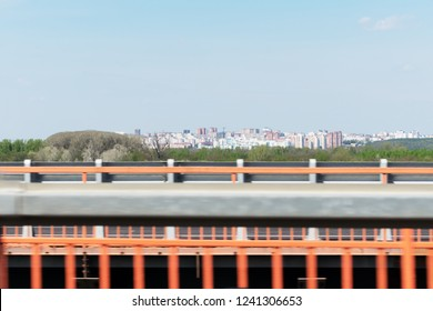 Blurred blockage on roadside with view of cityscape on background under blue sky