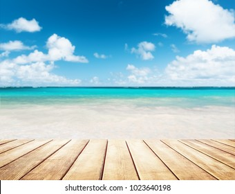 Blurred blue sky and sea with bokeh light and old wooden table background