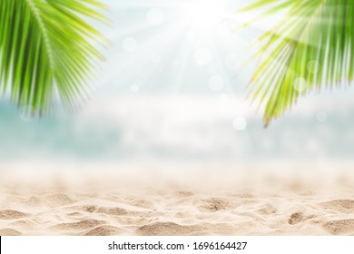 Blurred blue sky and sea with bokeh light and leaves of coconut palm tree. Landscape of tropical summer. Summer vacation concept.