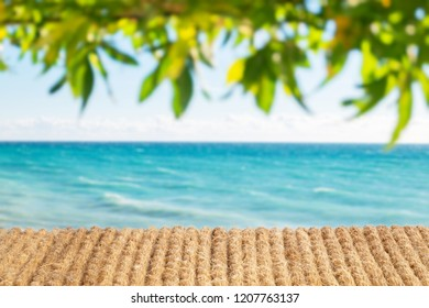 blurred blue sky and sea with tropical green leaves and bokeh. plank wrapped in a rope. Summer oceanic concept with table.