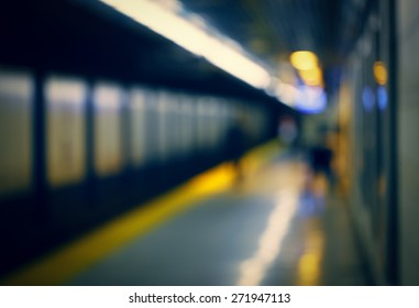 Blurred blurry soft focus background, interior of subway metro underground with passengers on a platform waiting