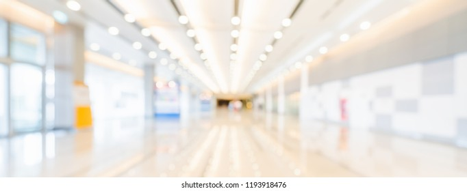 Blurred bokeh panoramic banner background of exhibition hall or convention center hallway. Business trade show event, modern interior architecture, or commercial tradeshow conference seminar concept