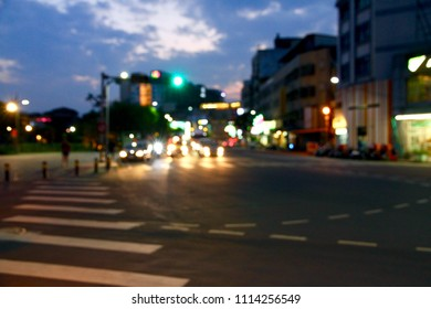The BLURRED, BOKEH PHOTO of the traffic light at the crossing road at evening.
