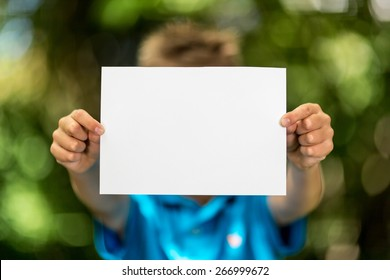 Blurred boy holding a blank piece of paper with copy space in front of her.