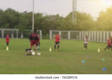 Blurred boys kicking football on the sports field